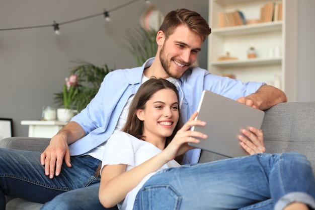 Jeune couple regardant du contenu multimédia en ligne sur une tablette assis sur un canapé dans le salon.