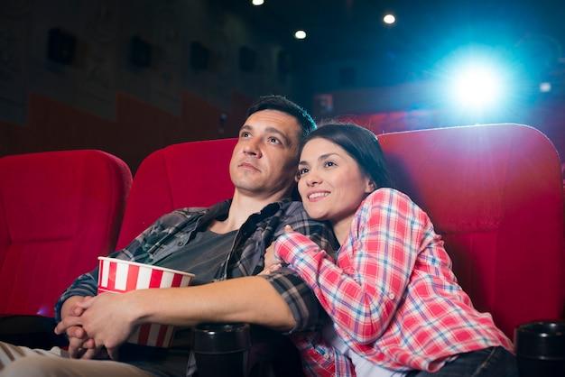 Jeune couple en regardant un film au cinéma
