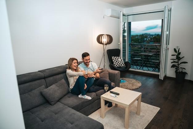 Jeune couple en regardant un film drôle dans leur maison.