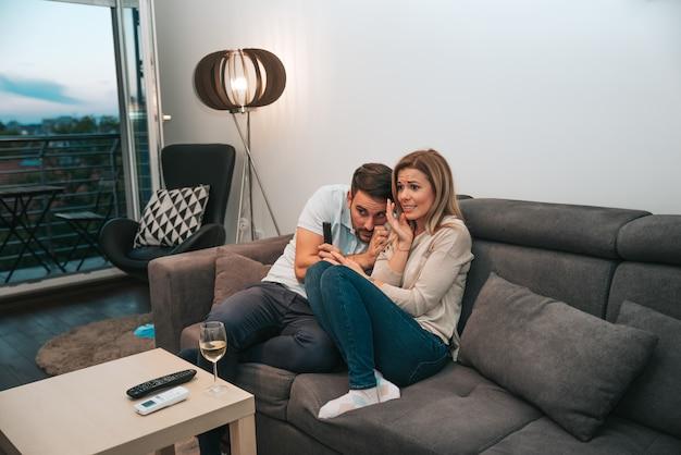 Jeune couple en regardant un film d'horreur à la maison.