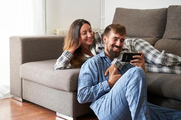 Jeune couple regardant mobile ensemble, habillé en pyjama à la maison. ils sont heureux et rient en vacances, appréciant d'être ensemble.