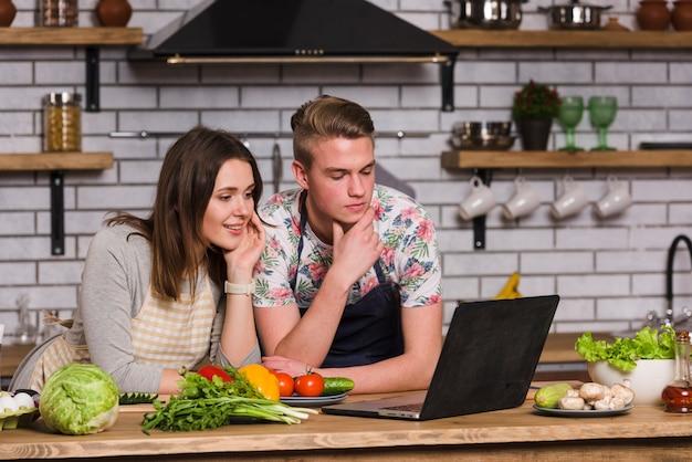 Jeune couple en regardant la recette sur un ordinateur portable