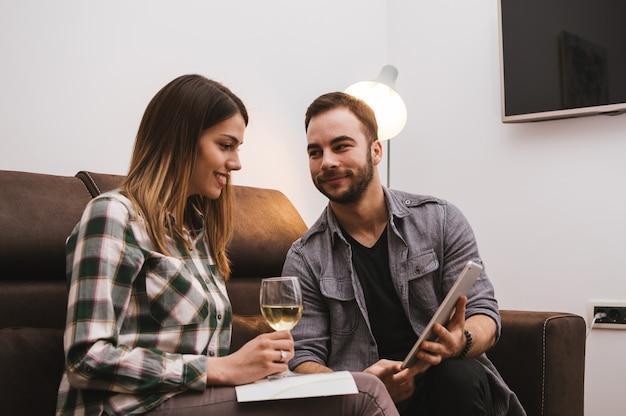 Jeune couple en regardant tablette et boire du vin à la maison