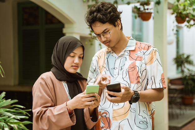 Jeune couple regardant les téléphones portables est très sérieux