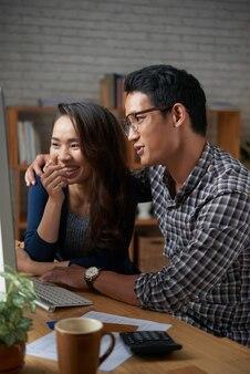Jeune couple en regardant des vidéos drôles sur le net