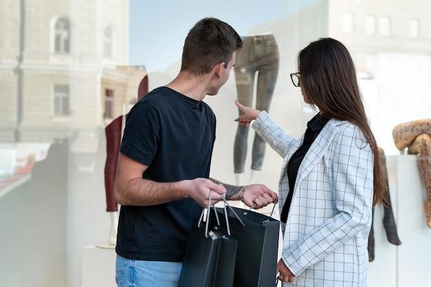 Jeune couple regardant la vitrine et montrant le doigt au mannequin.