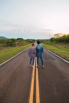 Jeune couple regarde l'horizon sur la route. accouplez-vous dos à l'autre sur la route.