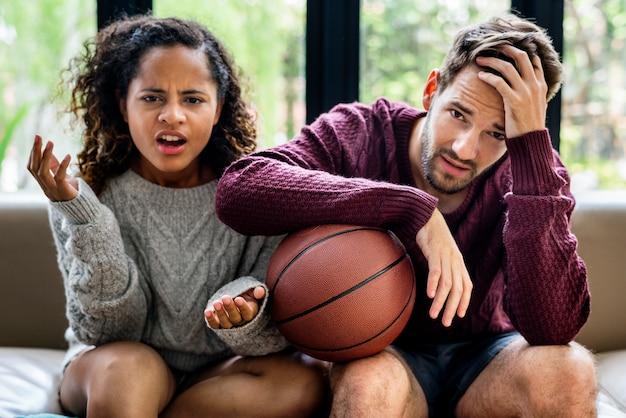 Jeune couple regarder match de basket à la maison