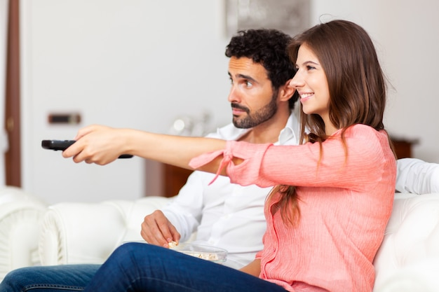 Jeune couple, regarder télé, et, manger, pop-corn