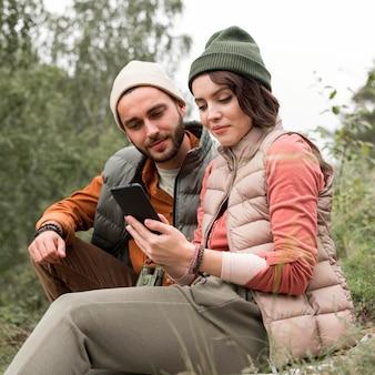 Jeune couple, regarder, téléphone, dans nature
