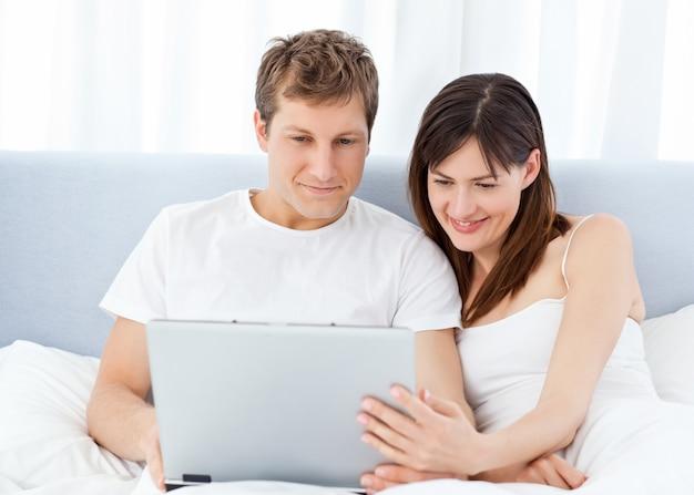 Jeune couple, regarder des vidéos sur leur ordinateur à la maison