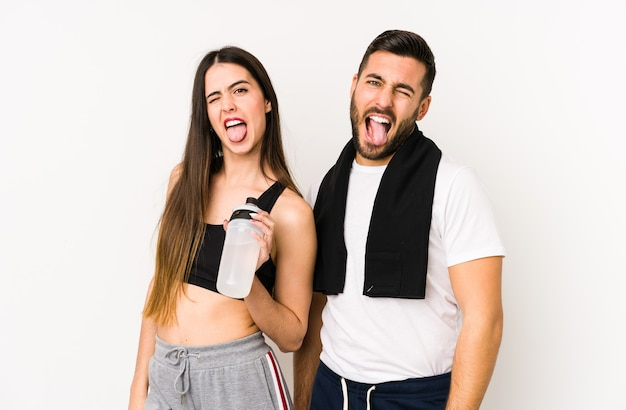Jeune couple de remise en forme caucasien isolé drôle et sympathique qui sort la langue.