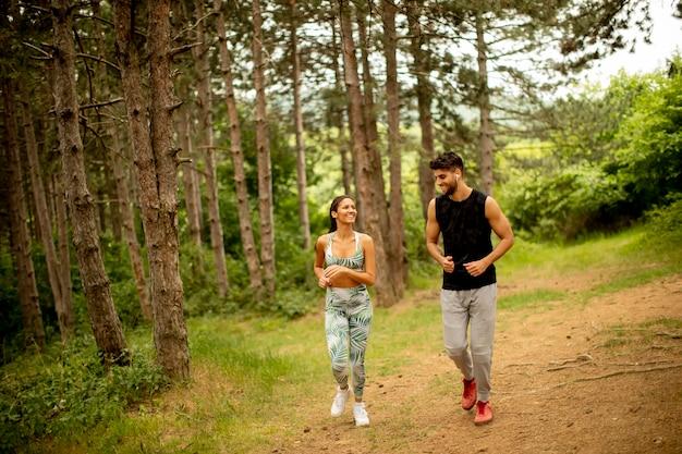 Jeune couple de remise en forme courant sur le sentier forestier un jour d'été