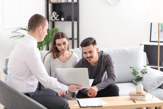 Jeune couple rencontre avec un agent d'assurance à la maison