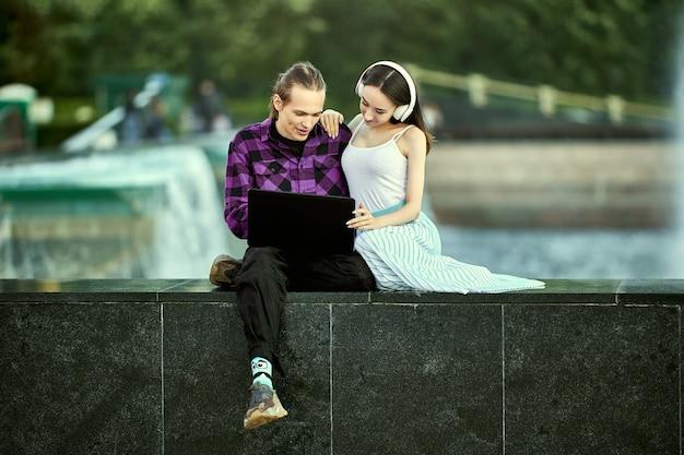 Un jeune couple à un rendez-vous en plein air utilise un ordinateur portable pour écouter de la musique avec des écouteurs sans fil
