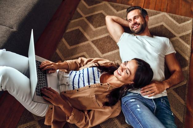 Un jeune couple de rêve s'allonge sur le sol sur le tapis à la maison. un couple marié se détend dans le salon. une femme avec un ordinateur portable est allongée sur un homme par terre. travail à domicile. shopping en ligne.