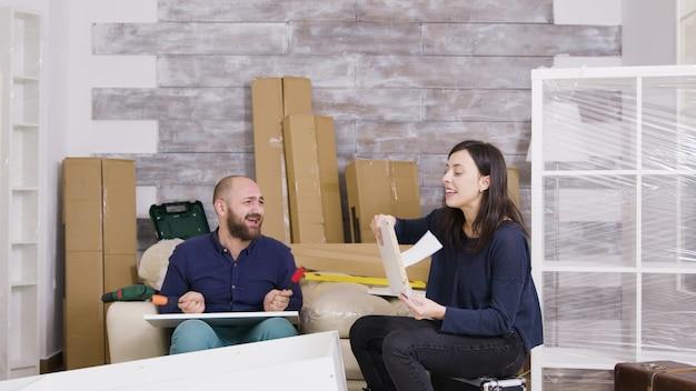 Jeune couple riant en assemblant des meubles dans leur appartement. fille lisant des instructions.