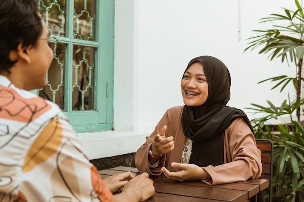 Jeune couple, rire, quoique, bavarder, face à face