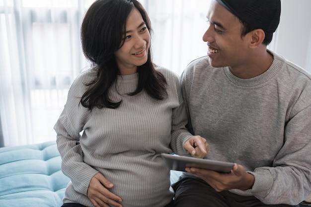 Jeune couple romantique assis sur le canapé tout en tenant une tablette numérique
