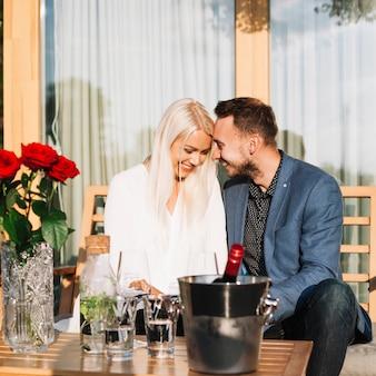 Jeune couple romantique assis derrière la table avec une bouteille de vin dans un seau à glace