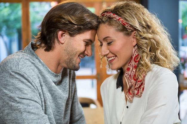 Jeune couple romantique assis tête à tête dans un café