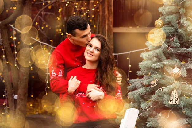 Jeune couple romantique décore l'arbre de noël à l'extérieur avant noël. garçon embrassant sa petite amie et elle souriant.