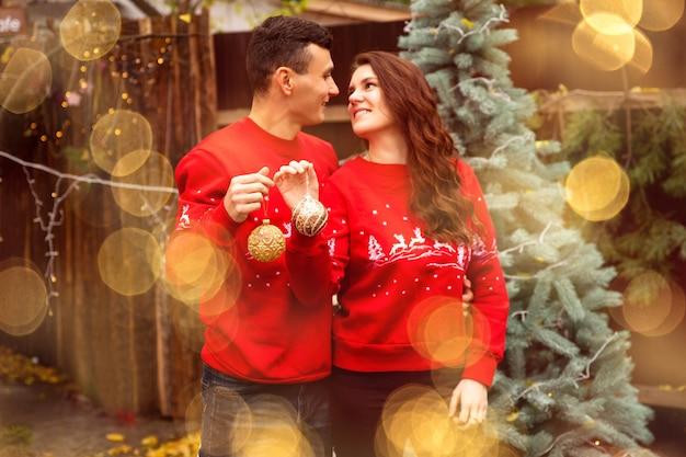 Jeune couple romantique décore l'arbre de noël à l'extérieur avant noël. ils tiennent des balles sur l'arbre et sourient.