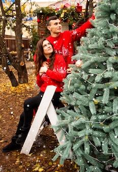 Jeune couple romantique décore l'arbre de noël à l'extérieur avant noël. profiter de passer du temps ensemble au réveillon du nouvel an.