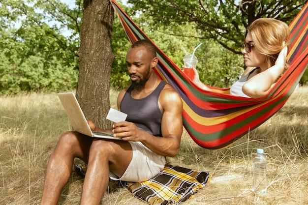 Jeune couple romantique international multiethnique à l'extérieur à la prairie en journée d'été ensoleillée. homme afro-américain et femme caucasienne ayant pique-nique ensemble. concept de relation, été.