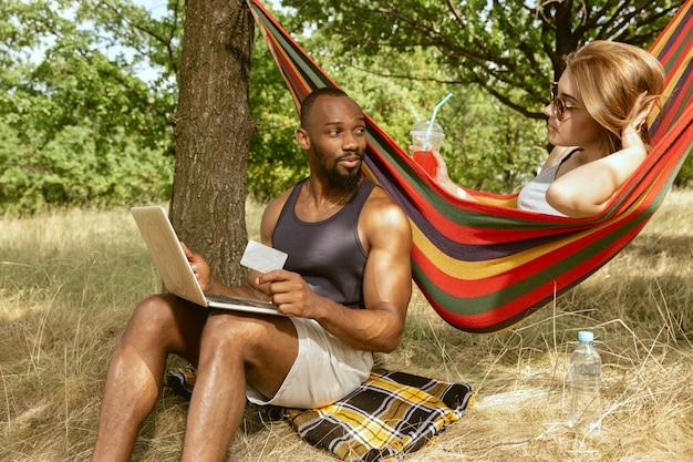 Jeune couple romantique international multiethnique à l'extérieur à la prairie en journée d'été ensoleillée. homme afro-américain et femme caucasienne ayant pique-nique ensemble. concept de relation, l'été.