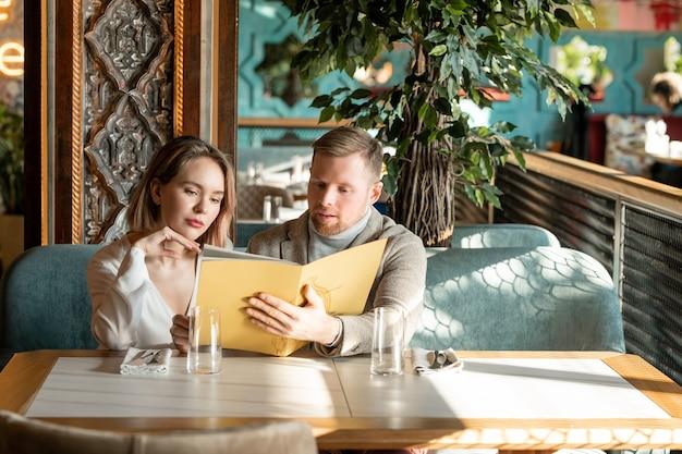 Jeune couple romantique à la recherche de menu dans un restaurant luxueux et discuter de ce qu'il faut choisir assis sur un canapé par table