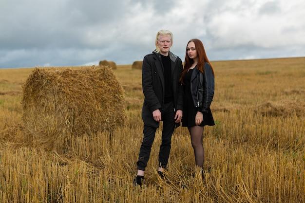 Un jeune couple romantique se tient dans un champ ouvert à côté de meules de foin par temps nuageux. photo de haute qualité