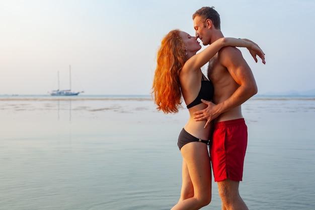 Jeune couple romantique sexy amoureux heureux sur la plage d'été ensemble s'amusant à porter des maillots de bain