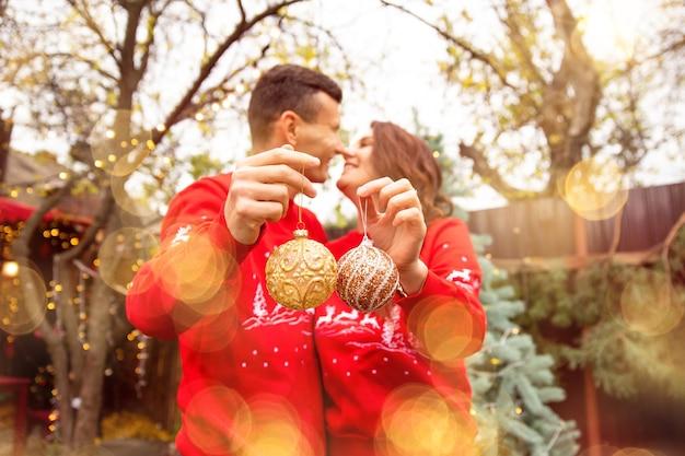 Jeune couple romantique tenant des boules sur l'arbre et s'embrassant sur le fond. ils décorent l'arbre de noël à l'extérieur avant noël.