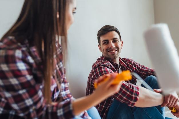Jeune couple avec rouleau faisant des réparations à domicile