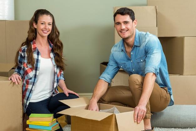 Jeune couple s'aidant lors du déballage de boîtes en carton dans la nouvelle maison