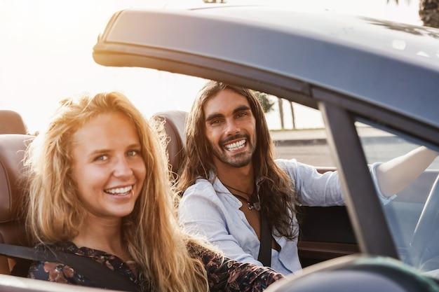 Jeune couple s'amusant dans une voiture décapotable en vacances d'été - focus sur le visage de l'homme