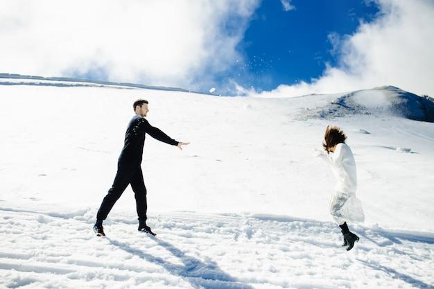 Jeune couple s'amuse et joue aux boules de neige