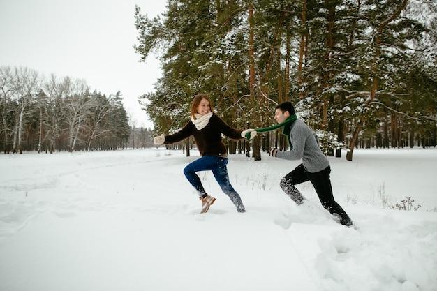Jeune couple s'amuser dans la forêt de pins enneigée. hiver.