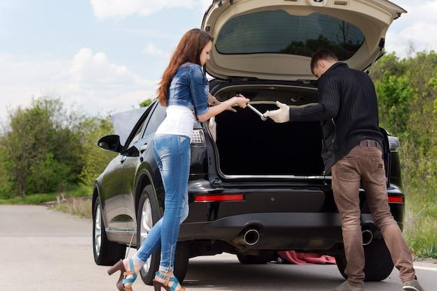 Jeune couple s'apprêtant à changer un pneu