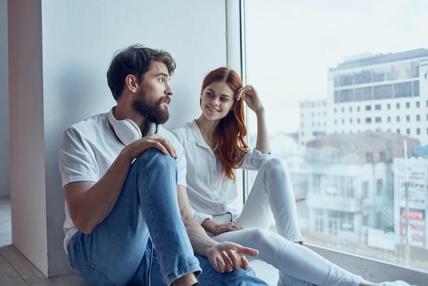 Un jeune couple s'asseoir près de la fenêtre avec des écouteurs romance joy