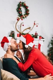 Jeune couple s'embrassant sur le canapé