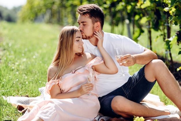 Jeune couple s'embrassant dans un vignoble.