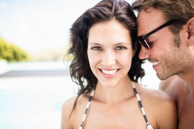 Jeune couple s'embrassant près de la piscine à la journée ensoleillée