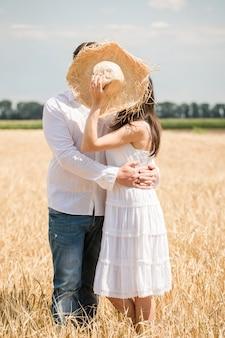 Jeune couple s'embrassant se cachant derrière le chapeau