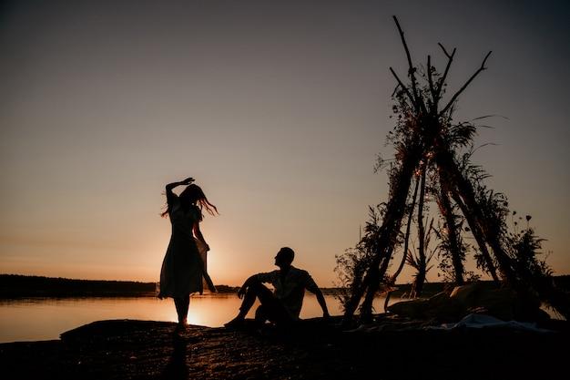 Jeune couple s'embrasse dans l'eau au coucher du soleil. deux silhouettes contre le soleil. histoire d'amour romantique. wigwam sur la pierre.