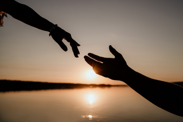 Jeune couple s'embrasse dans l'eau au coucher du soleil. deux silhouettes de mains contre le soleil. histoire d'amour romantique.