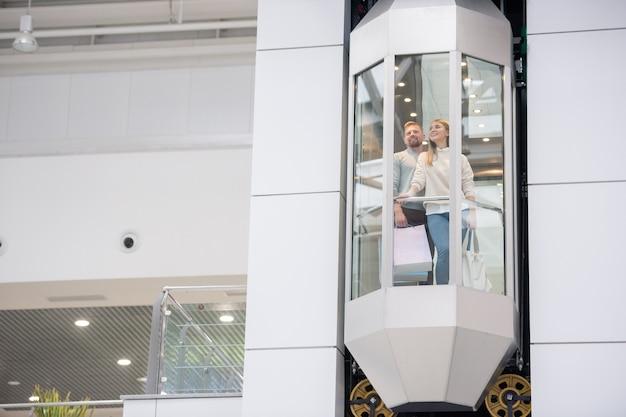 Jeune couple avec des sacs en papier debout dans l'ascenseur tout en se déplaçant vers le haut à l'intérieur d'un grand centre commercial contemporain pendant le shopping