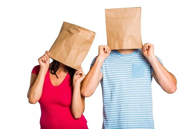 Jeune couple avec des sacs sur la tête