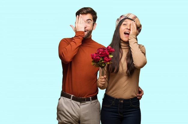 Jeune couple, saint valentin, crier, heureux, couvrir, face, à, main